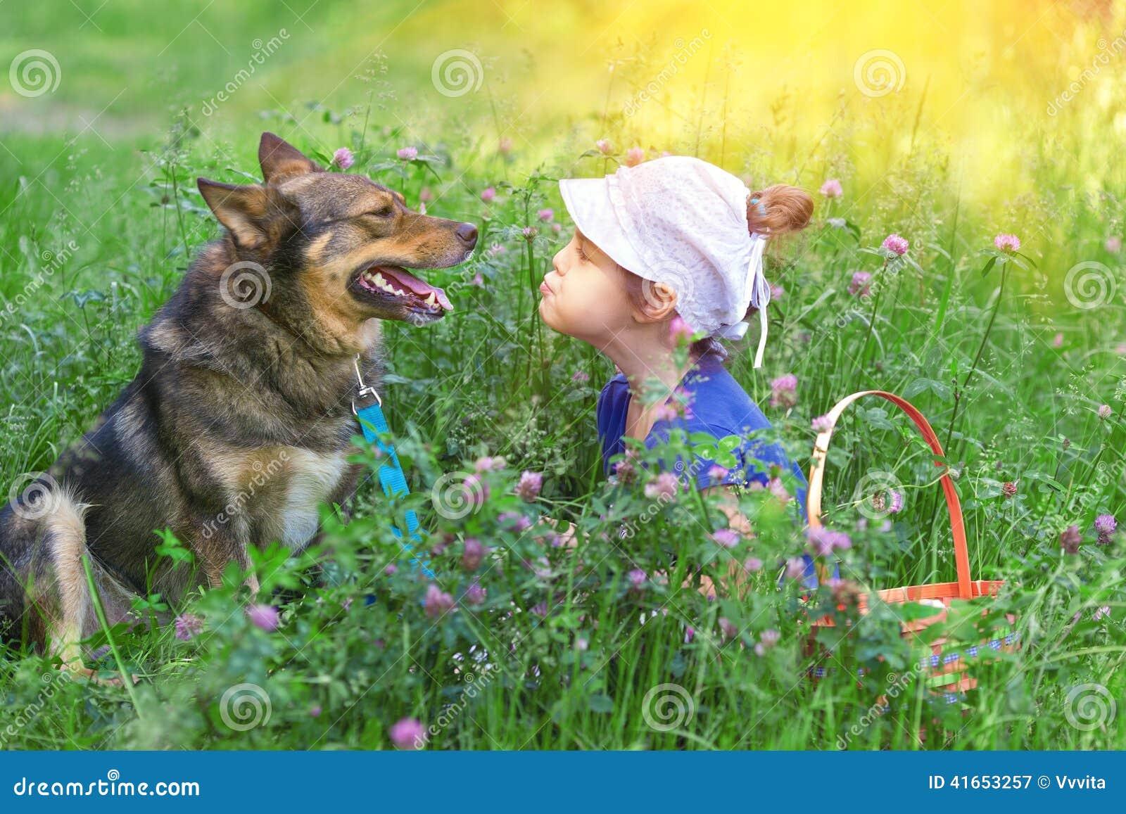 Маленькая девочка и собака сидя в лужайке клевера