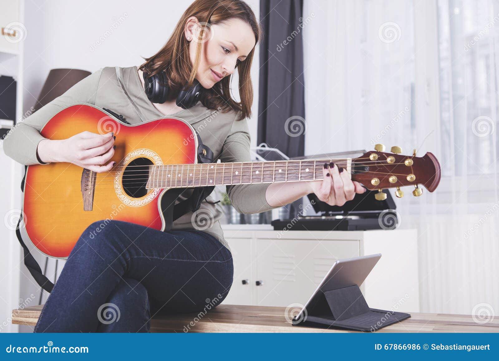 Маленькая девочка на софе играя гитару
