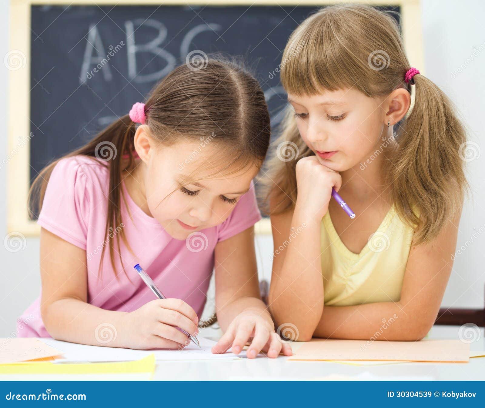 Маленькая девочка пишет используя ручку