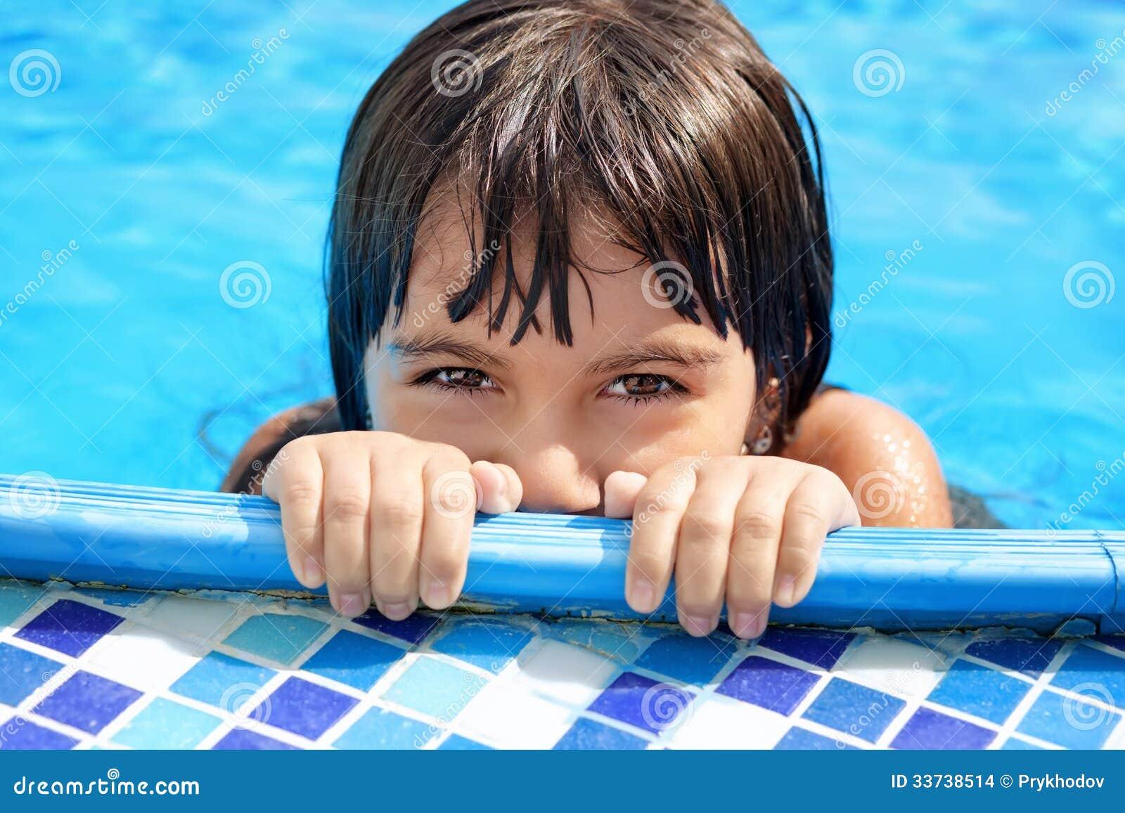 Маленькая девочка при красивые глаза peeking из бассейна