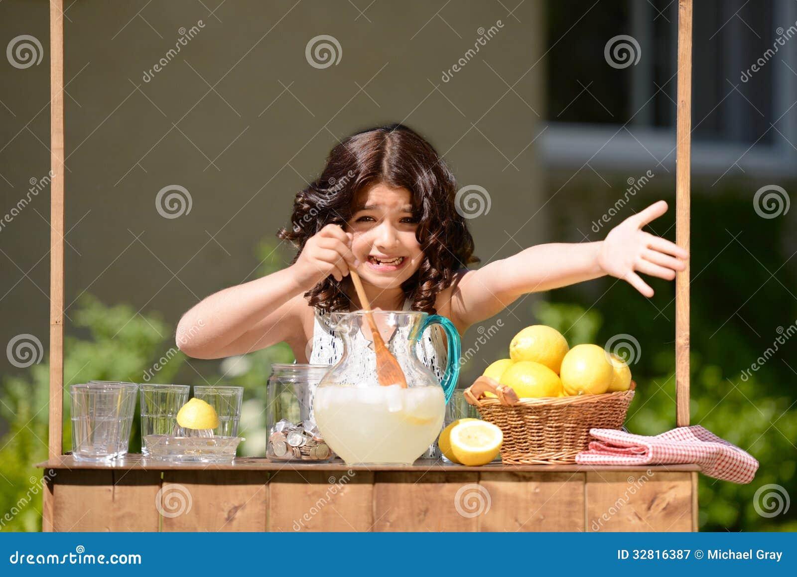 Маленькая девочка пробуя продать лимонад