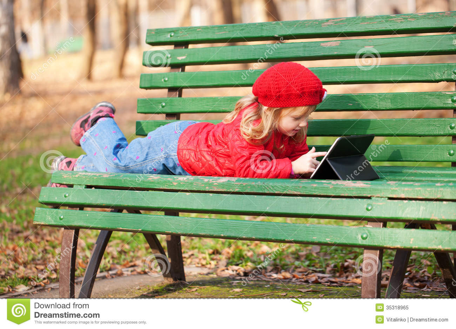 Маленькая девочка работая с ПК таблетки в парке.