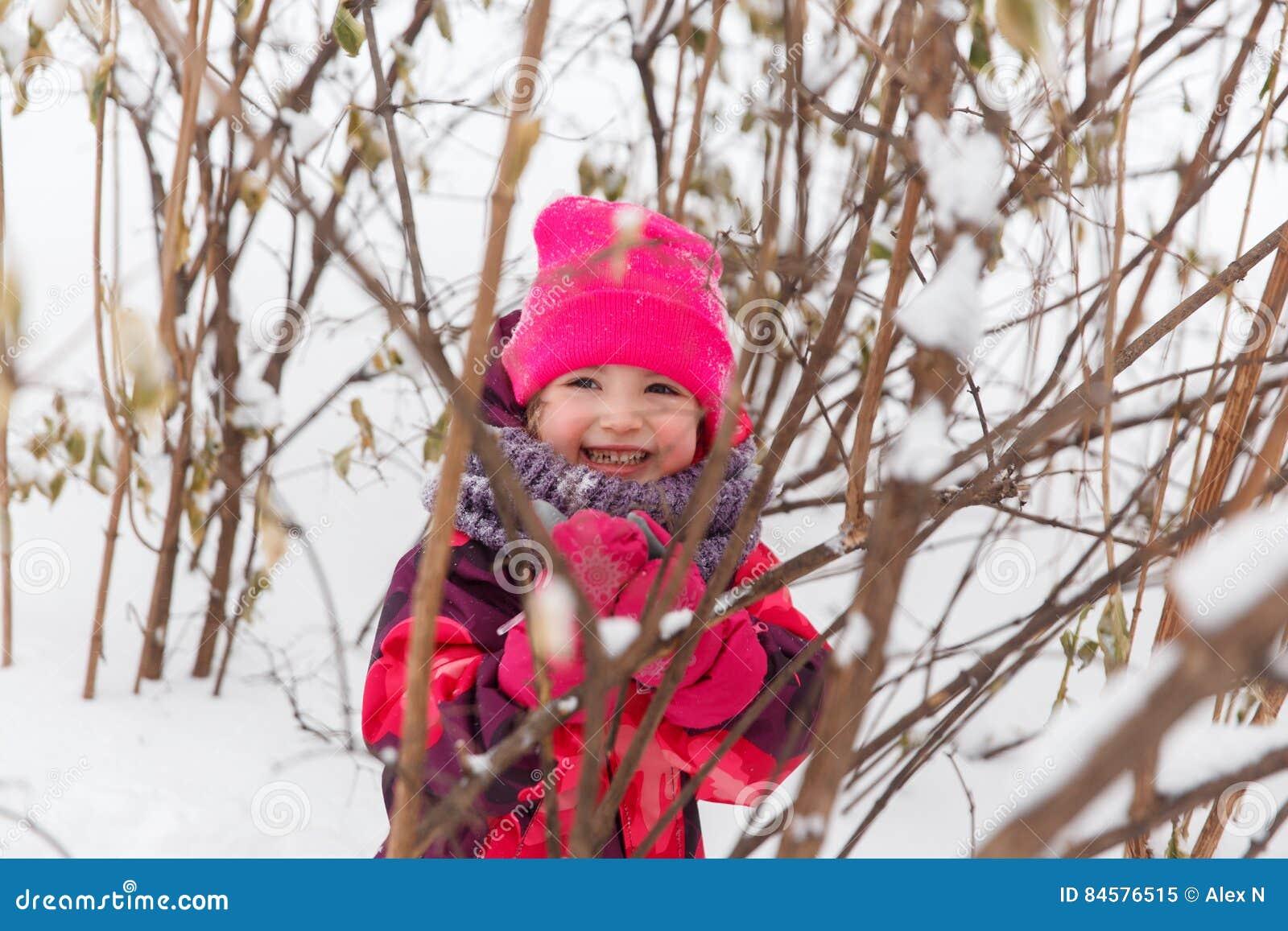 Маленькая девочка среди кустов зимы