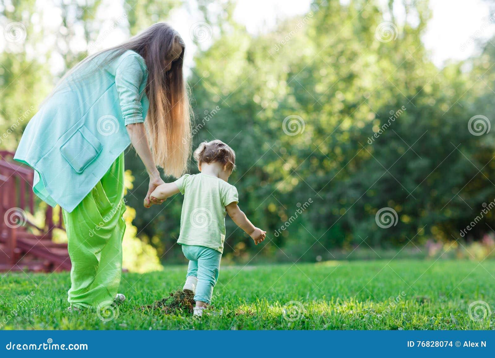 Маленькая девочка с матерью идет на лужайку