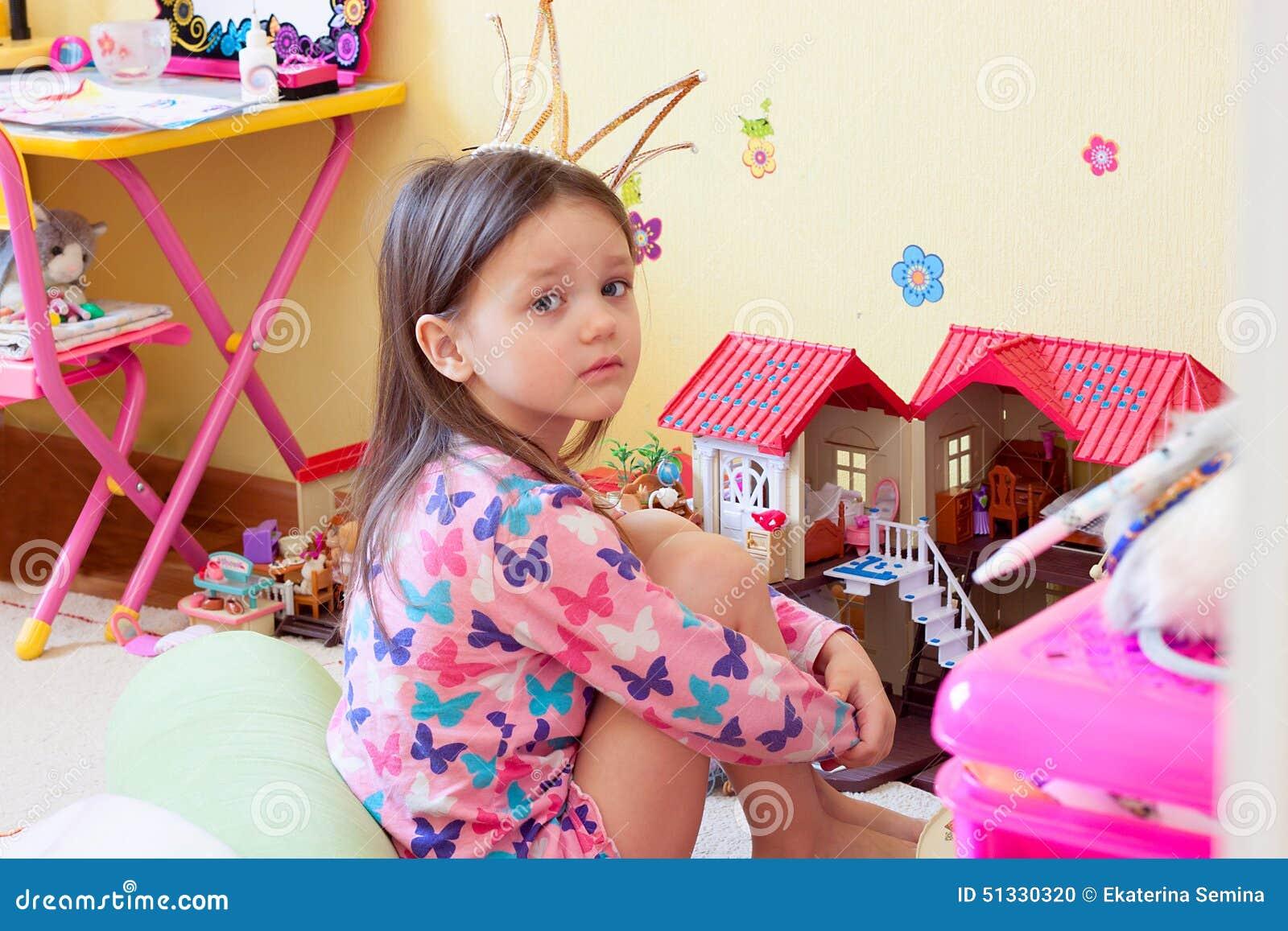 Маленькая девочка уныла среди игрушек