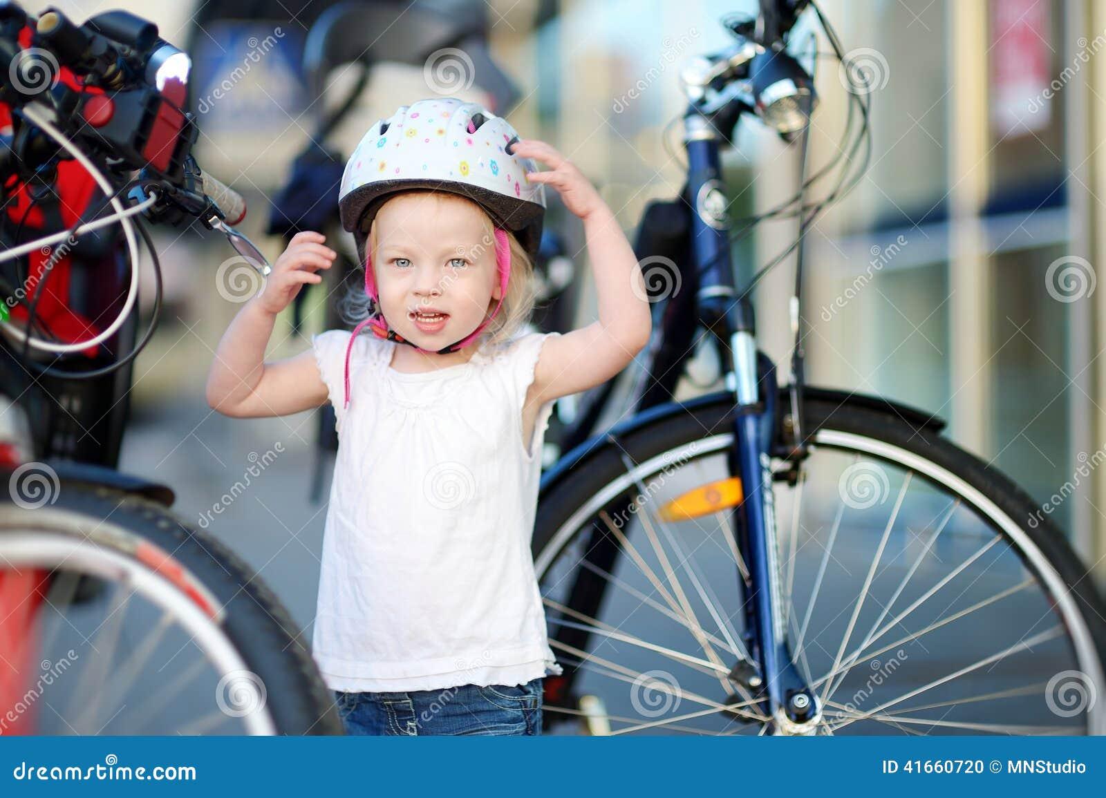 Маленькая девушка малыша готовая для того чтобы ехать велосипед