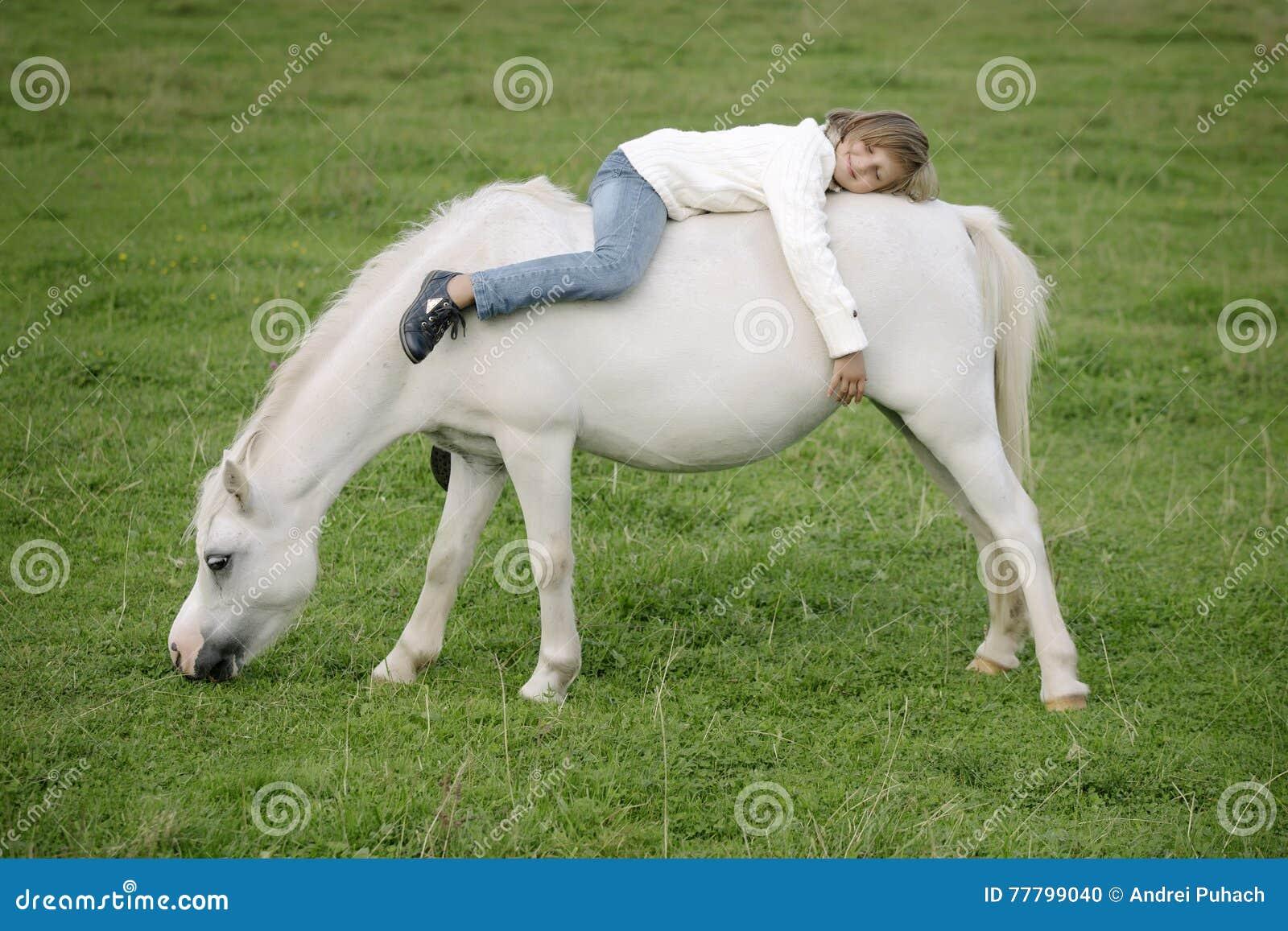 Маленькая маленькая девочка в белом свитере и джинсах лежа ОН назад на задней части белой лошади Портрет образа жизни