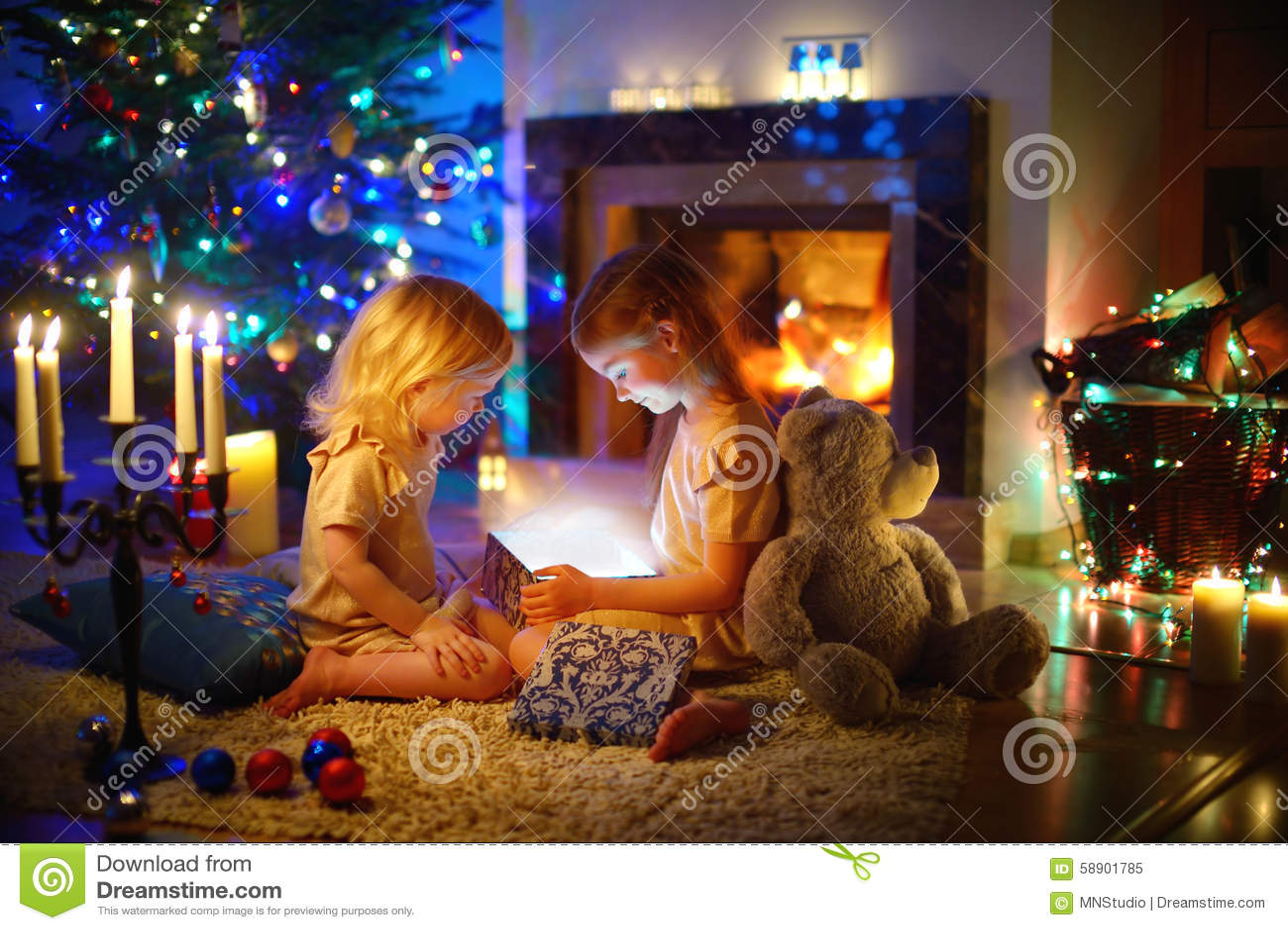 Маленькие девочки раскрывая волшебный подарок рождества