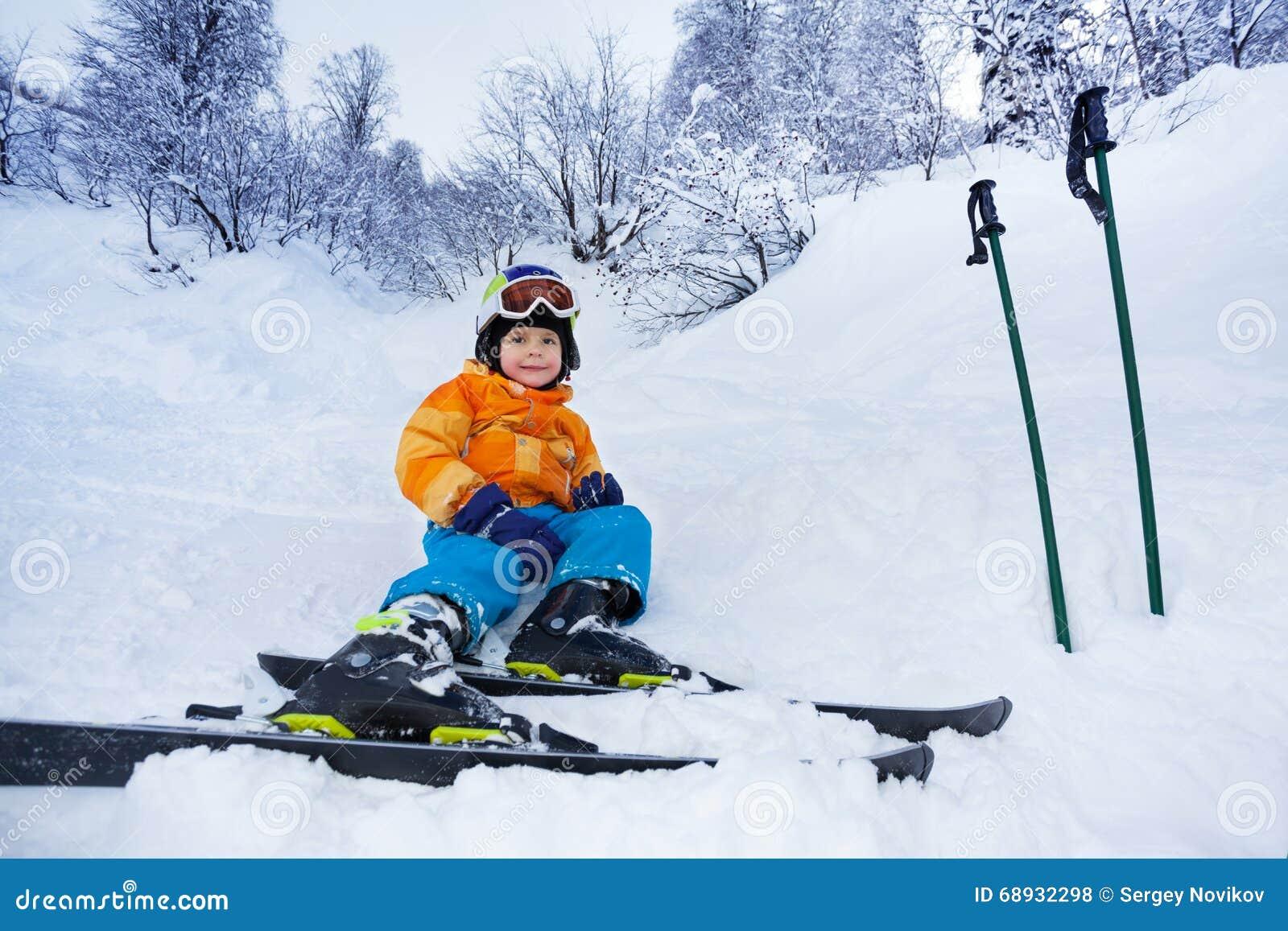Маленькие остатки мальчика лыжника в обмундировании лыжи носки снега