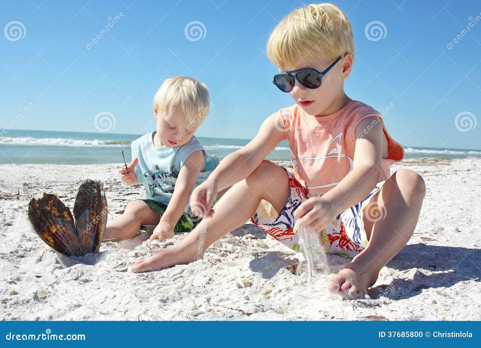 Маленькие ребеята играя в песке на пляже