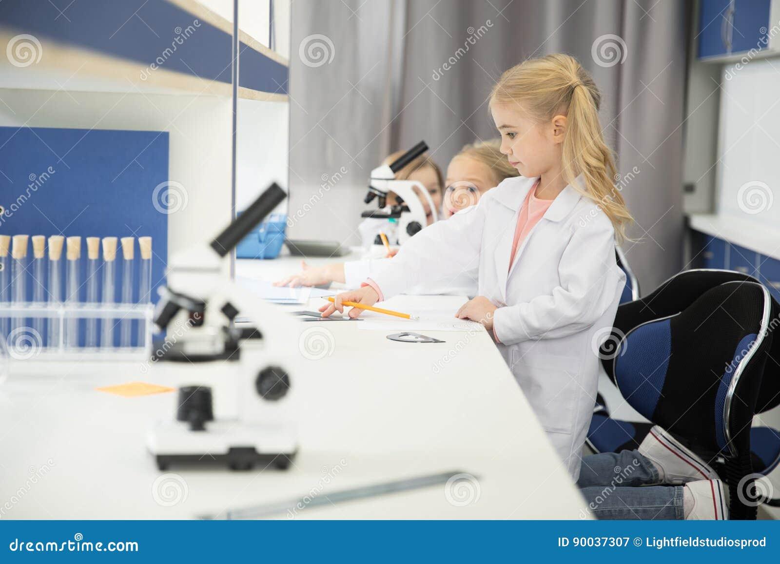 Маленькие ребеята нося пальто и изучать лаборатории