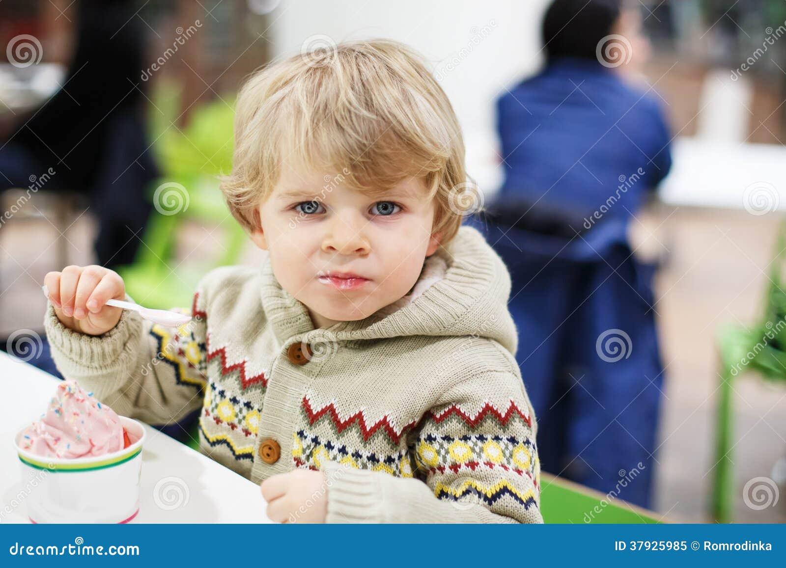 Маленький белокурый мальчик малыша есть мороженое