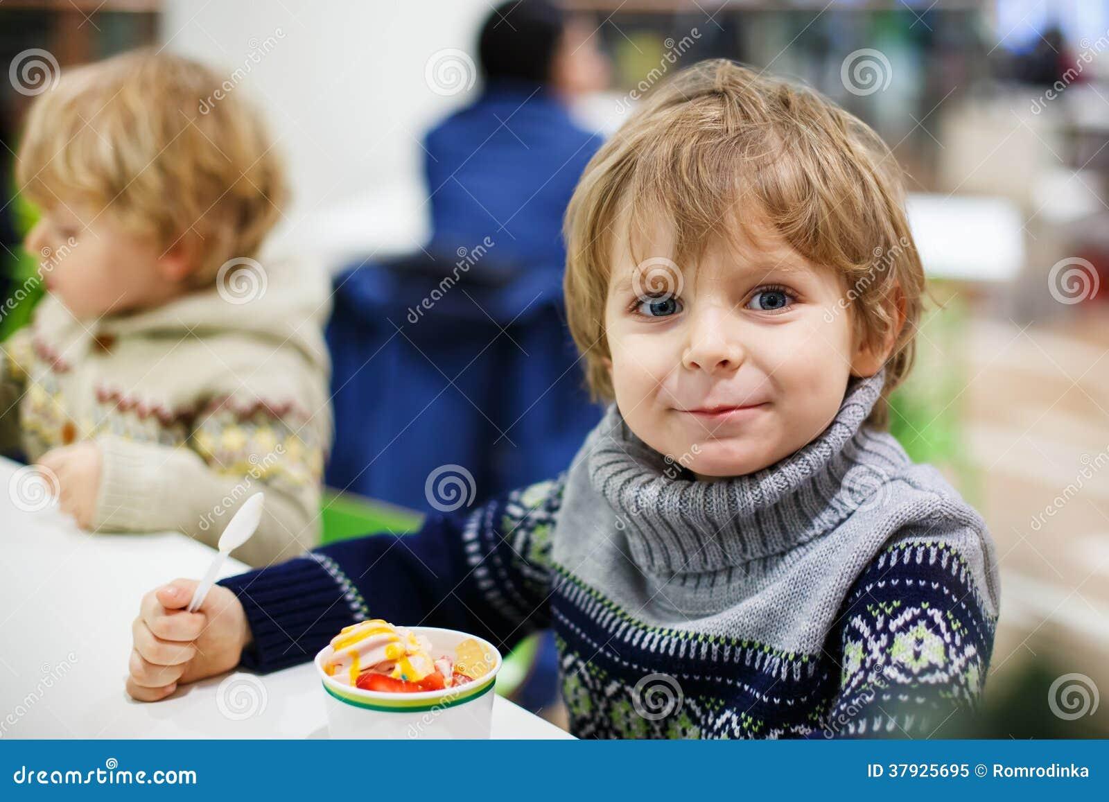 Маленький белокурый мальчик малыша есть торговый центр iin мороженого