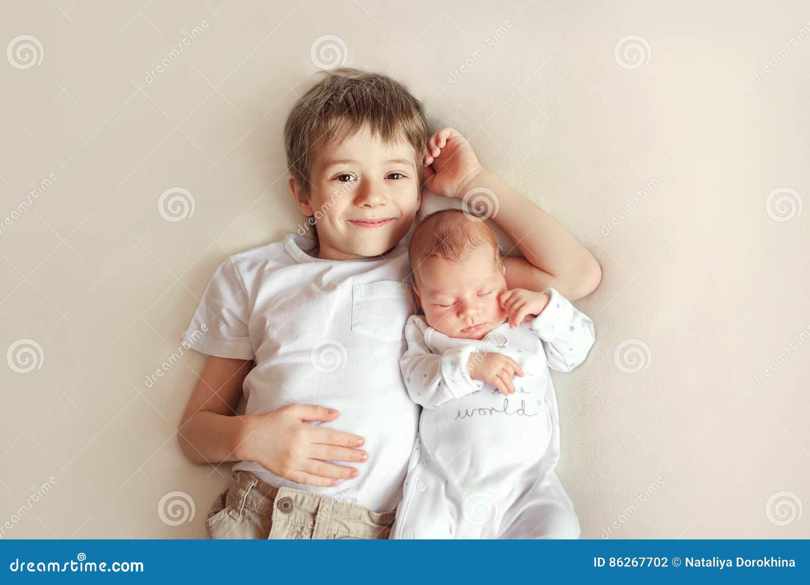 Маленький брат обнимая ее newborn младенца Ребенк малыша встречая новый отпрыска Милый мальчик и ребёнок новорожденного ослабляют
