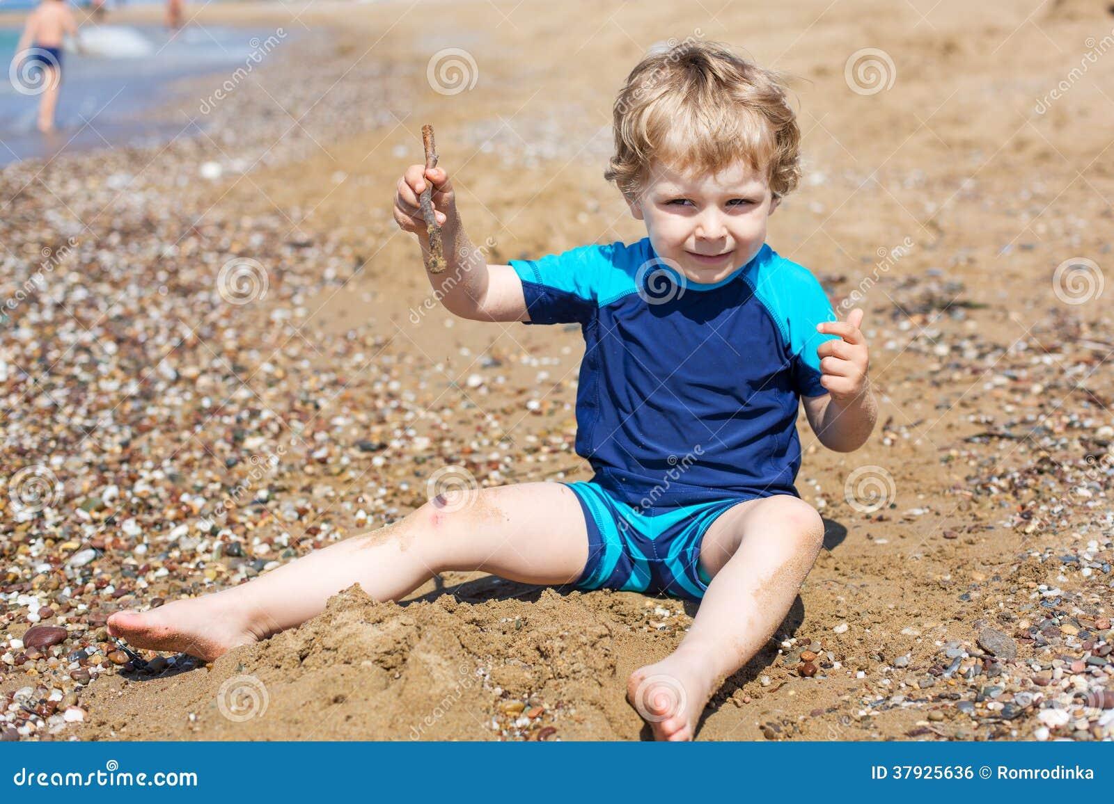 Маленький мальчик малыша играя с песком и камнями на пляже