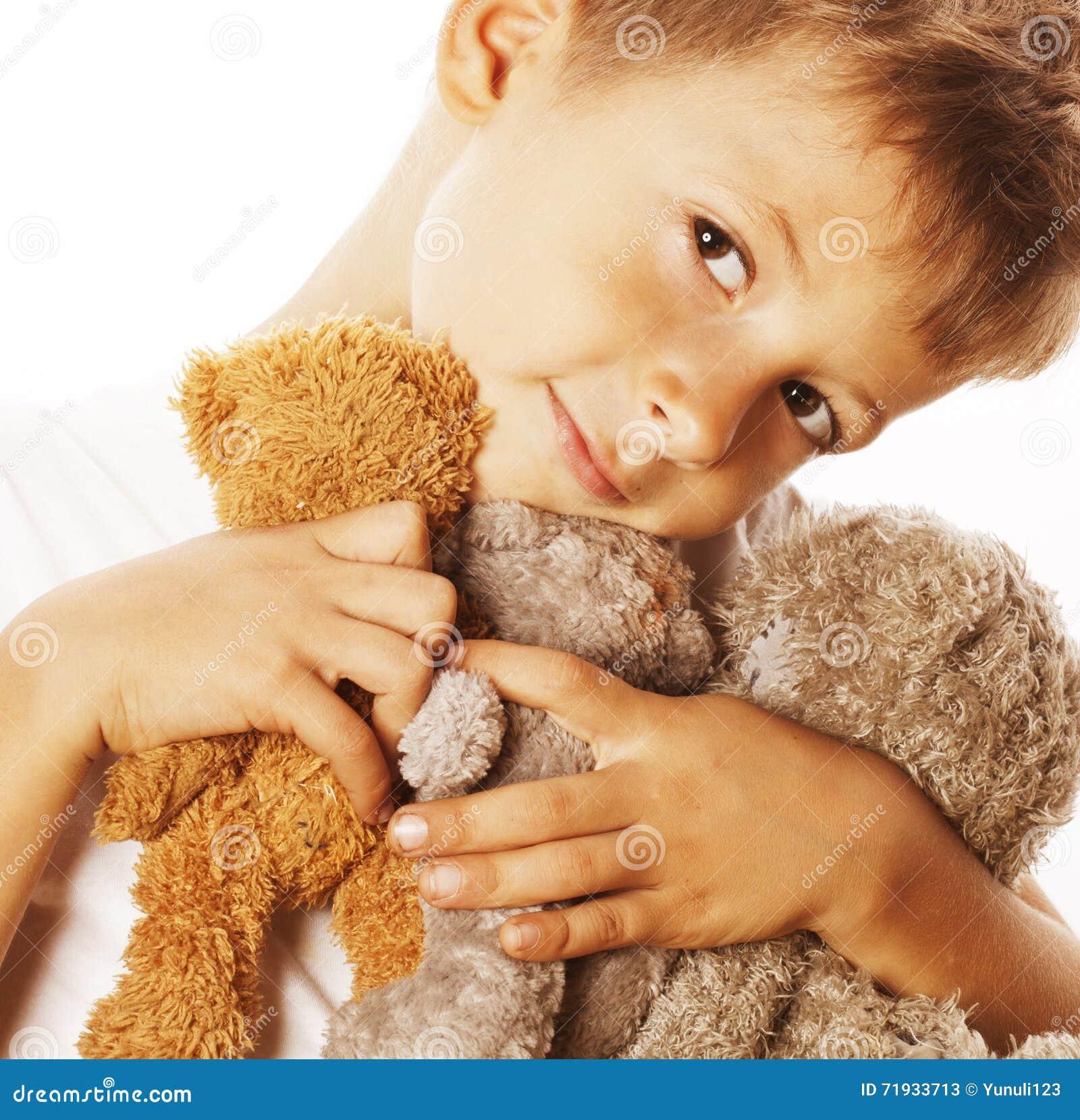 Маленький милый мальчик с обнимать много плюшевых медвежоат изолированный близко вверх