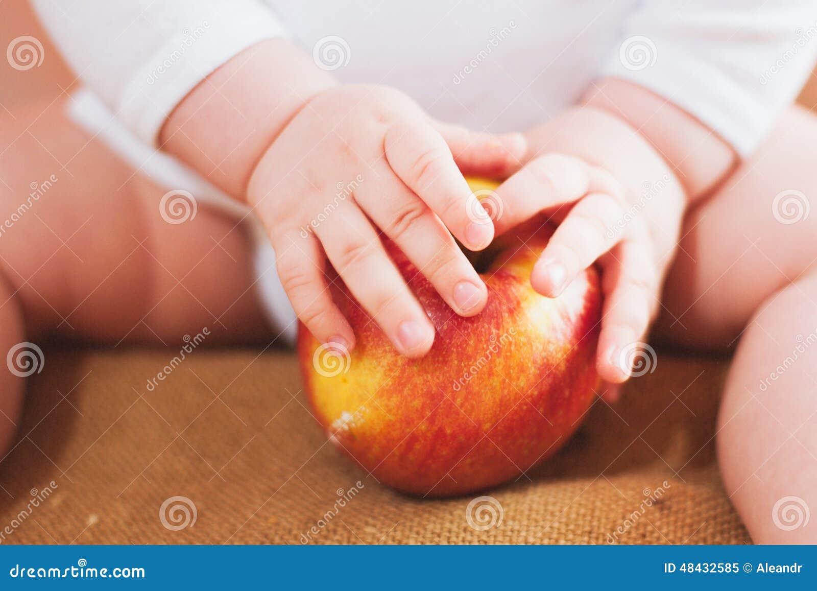 Маленький младенец держит красное яблоко