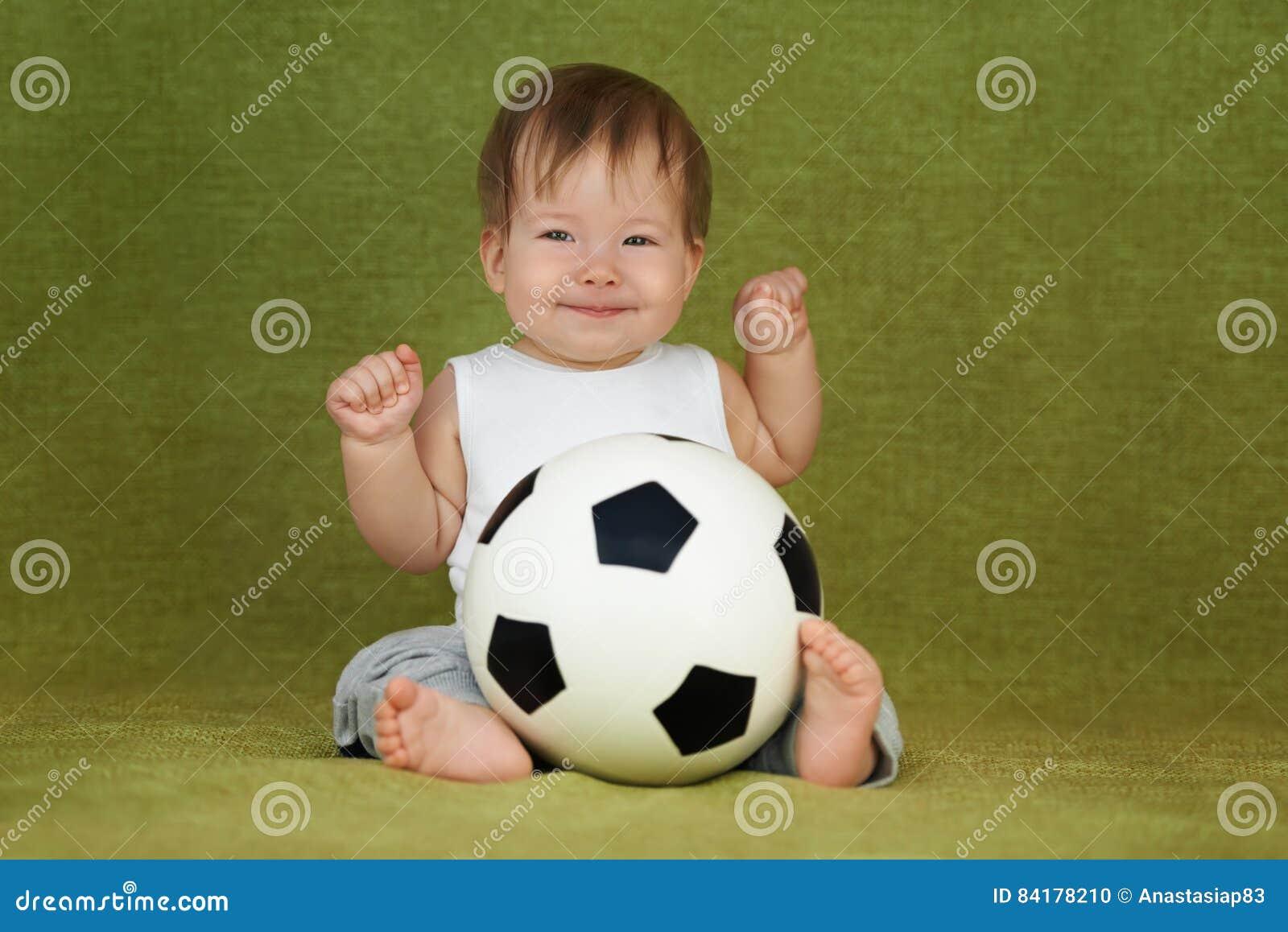 Маленький ребенок как раз получал шарик футбола как настоящий момент