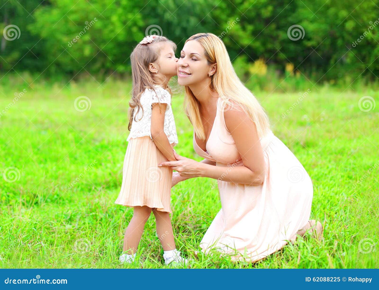 Маленький ребенок дочери целуя любящую мать в летнем дне, счастливую семью