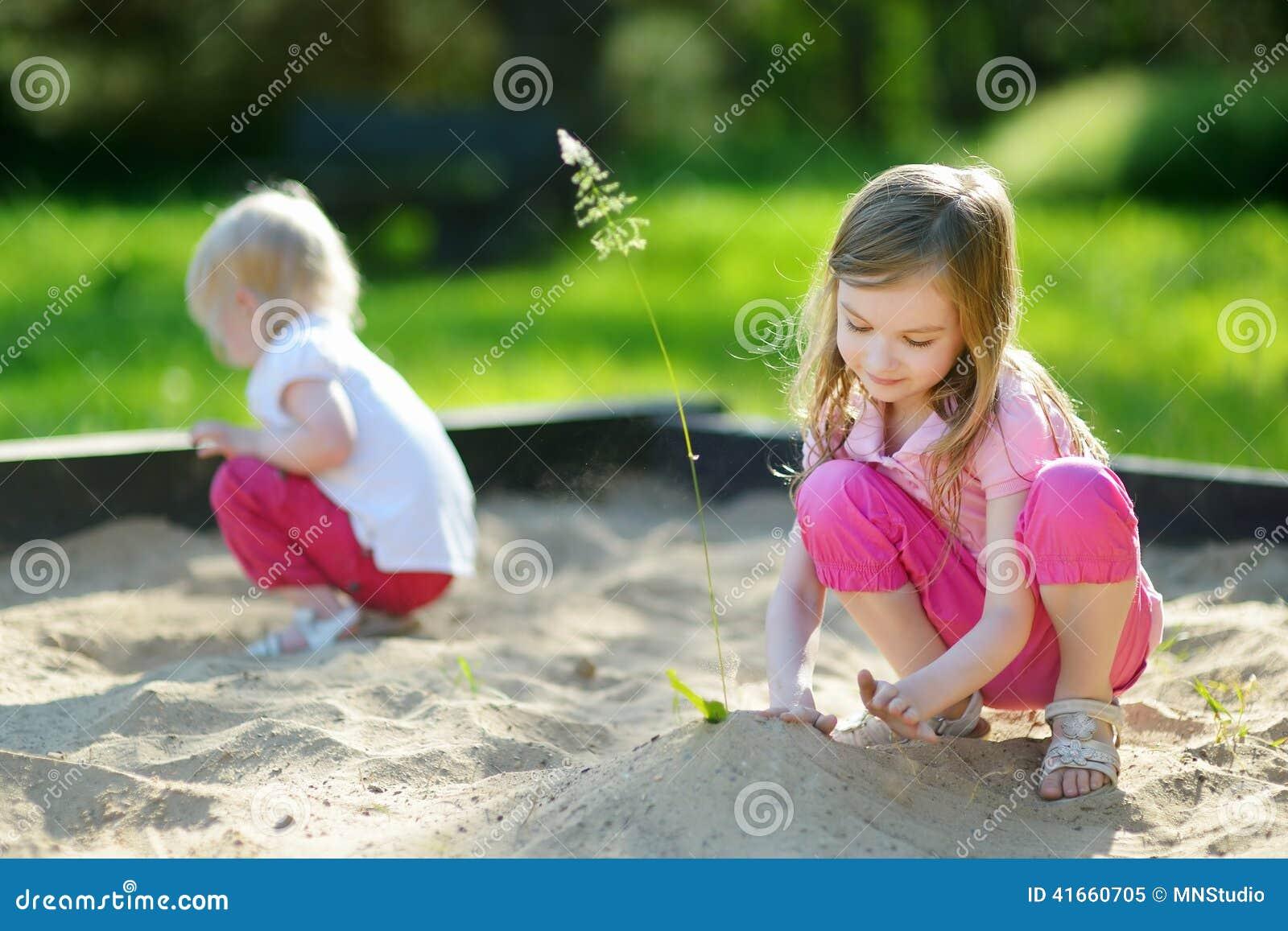 2 маленьких сестры играя в ящике с песком