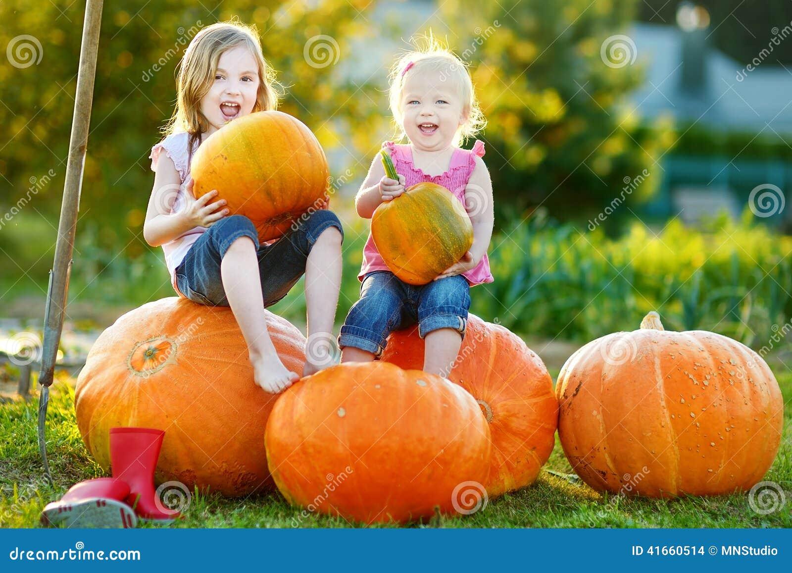 2 маленьких сестры сидя на огромных тыквах