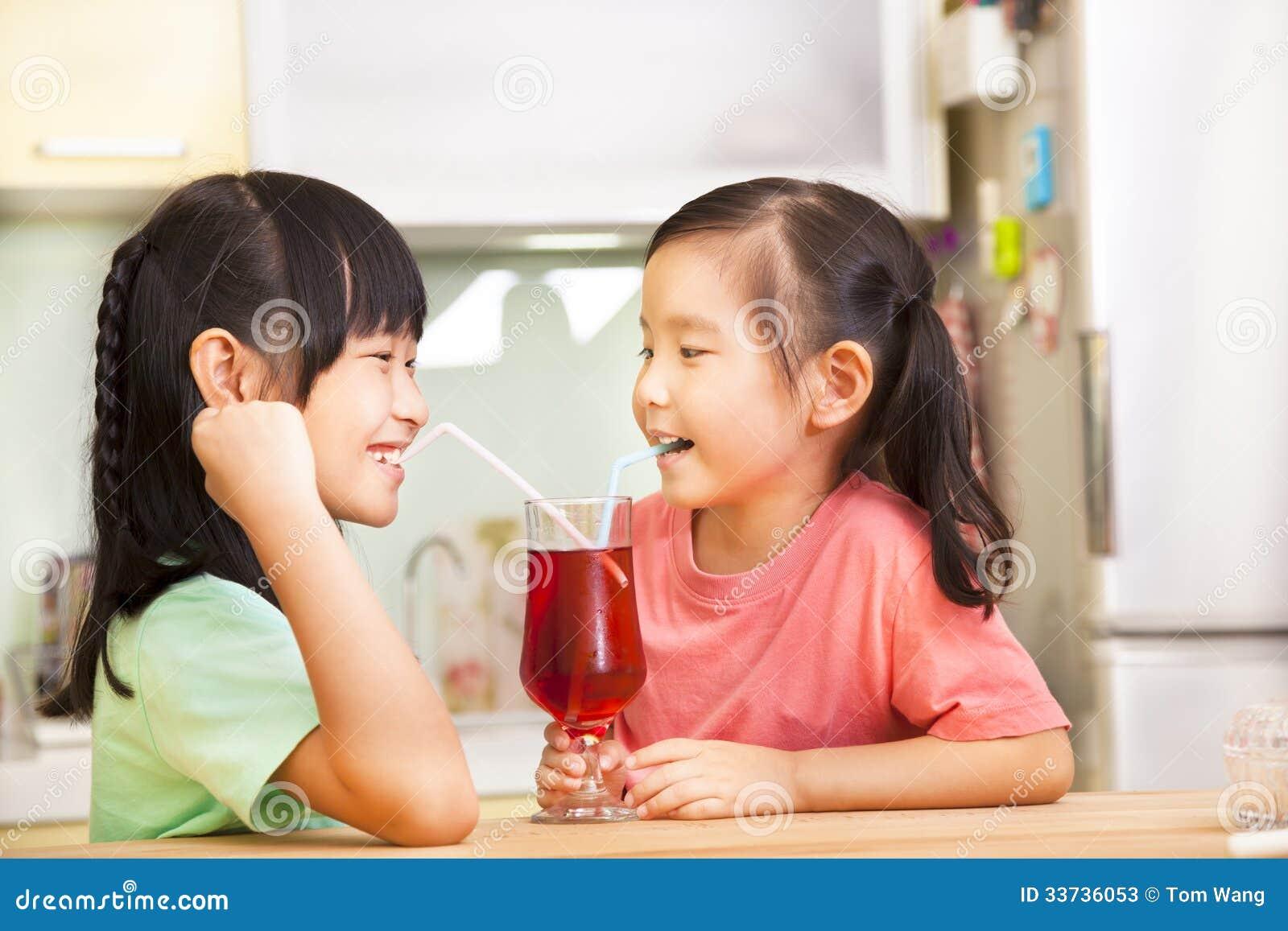 2 маленькой девочки выпивая сок дома