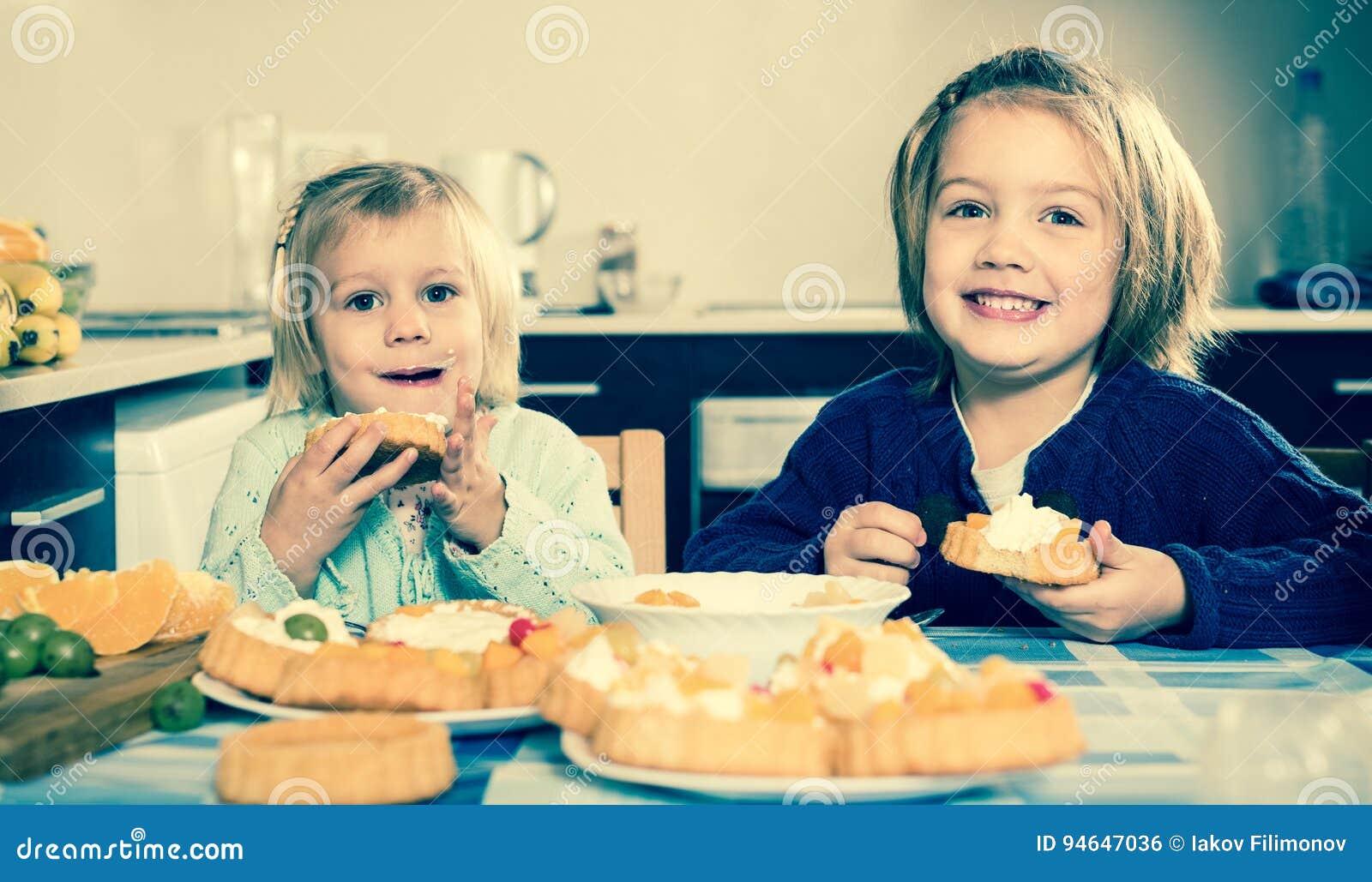 2 маленькой девочки наслаждаясь печеньем с сливк