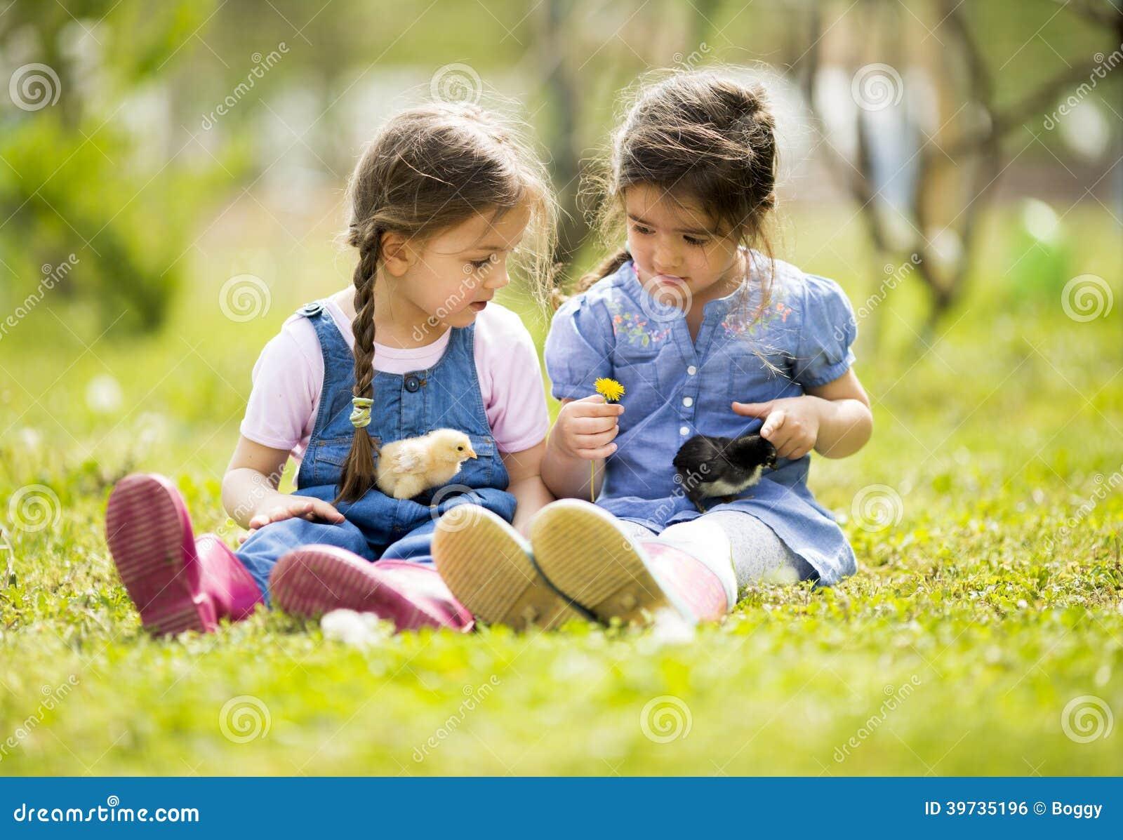 2 маленькой девочки с цыплятами