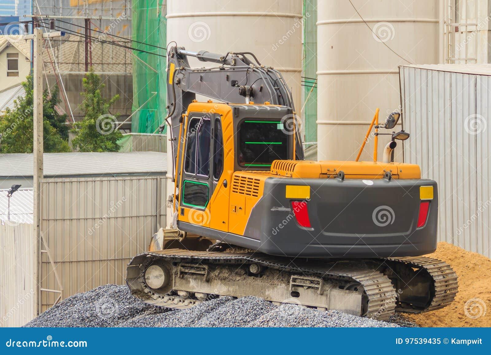 Малый желтый экскаватор работая на строительной площадке Мини ба