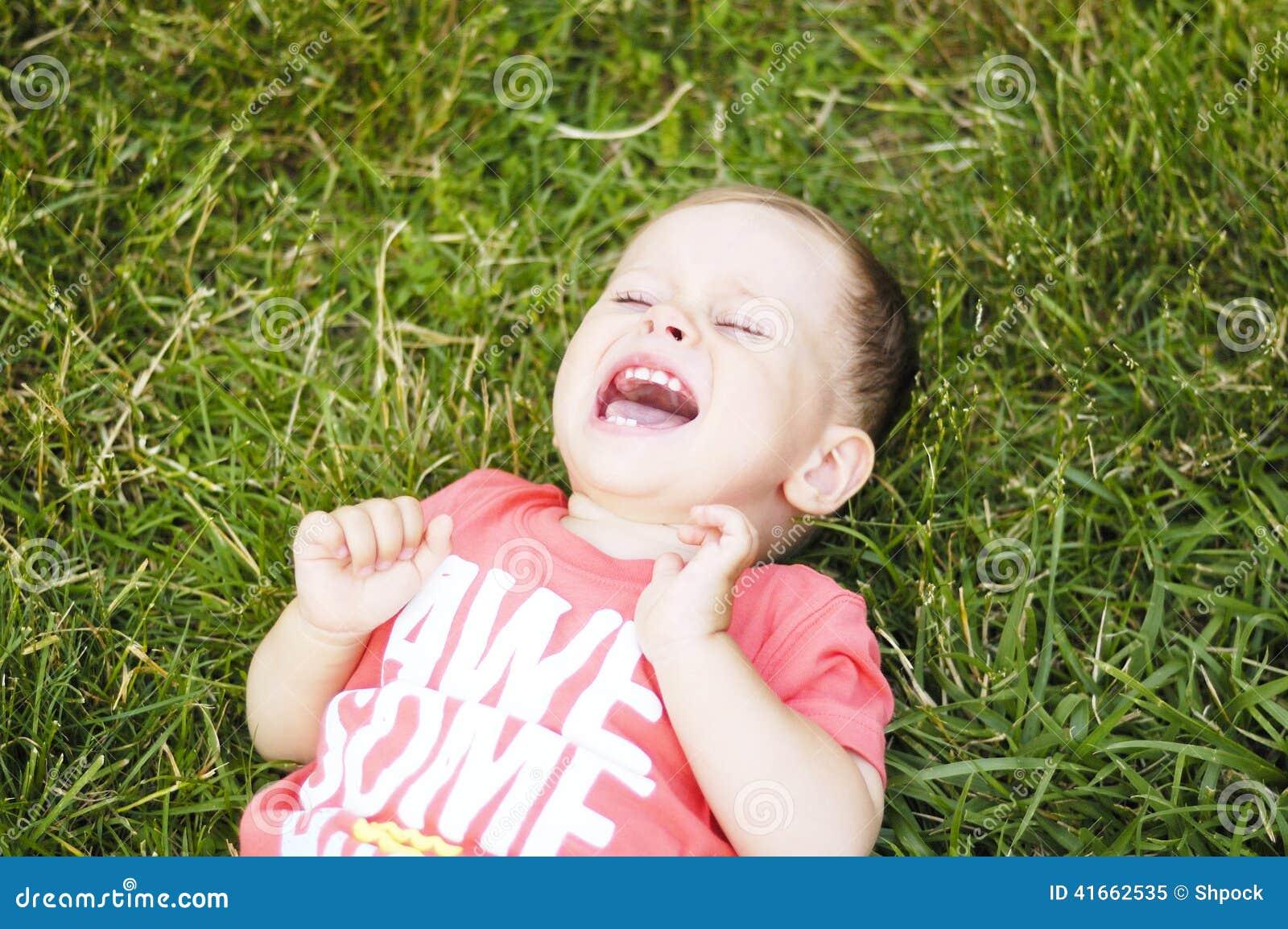 Малый плача мальчик на траве