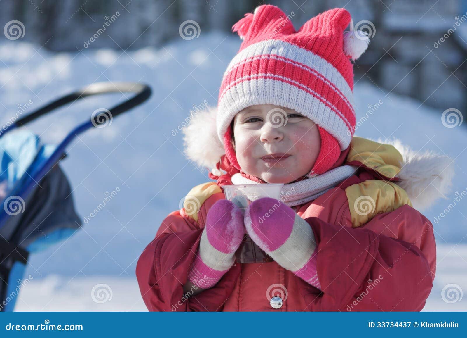 Малый ребенок выпивает горячее питье в зиме