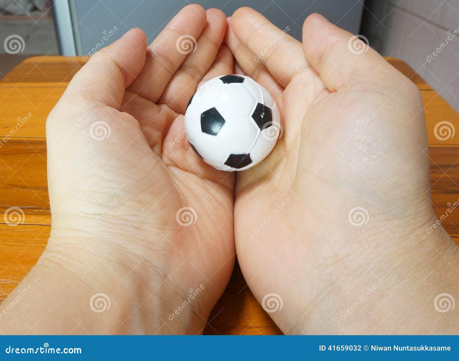 Малый футбольный мяч в обоих рука