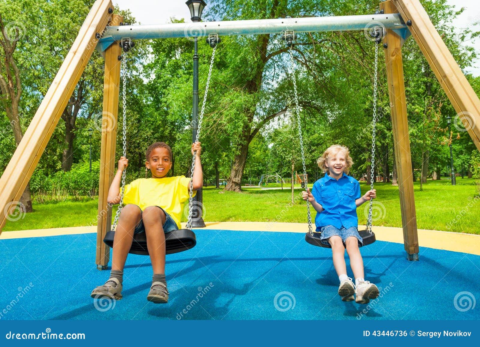 2 мальчика отбрасывают совместно и держат цепи качаний