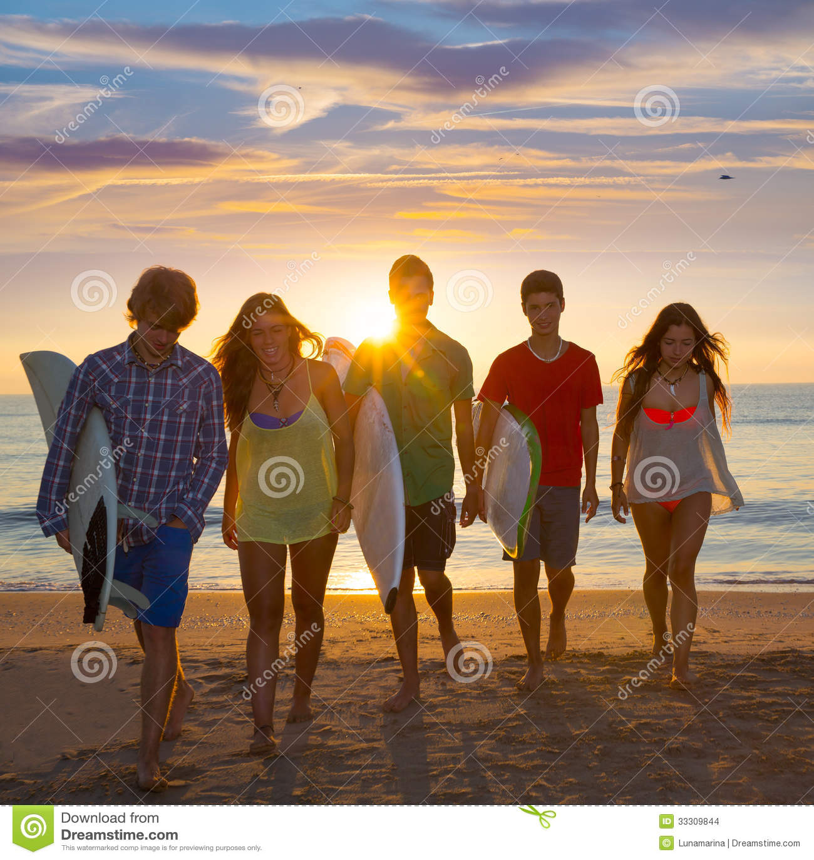 Мальчики и девушки серферов собирают идти на пляж