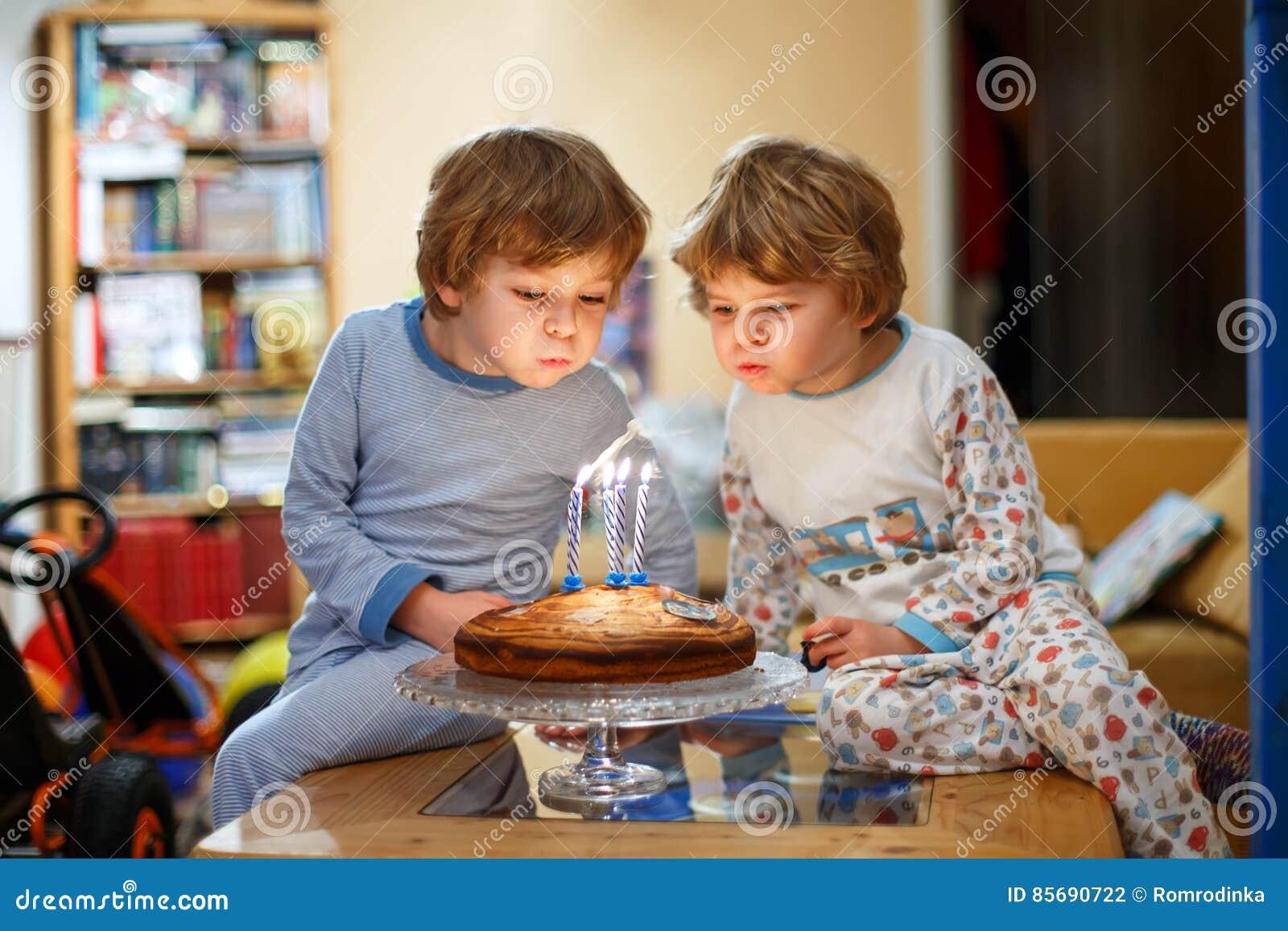Мальчики маленького ребенка дублируют праздновать день рождения и дуть свечи на торте