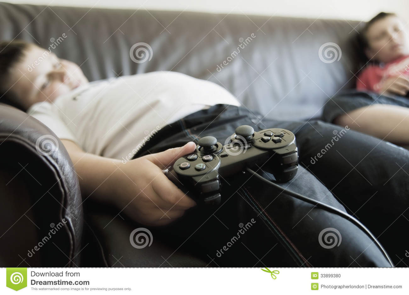 Мальчики спать на софе пока держащ консоли игр