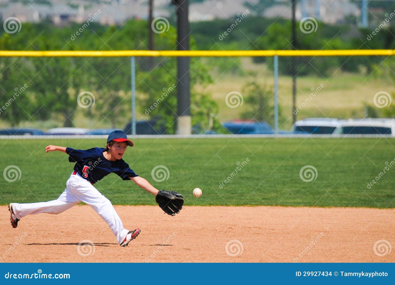 Мальчик Малой лиги достигает вне для того чтобы уловить шарик