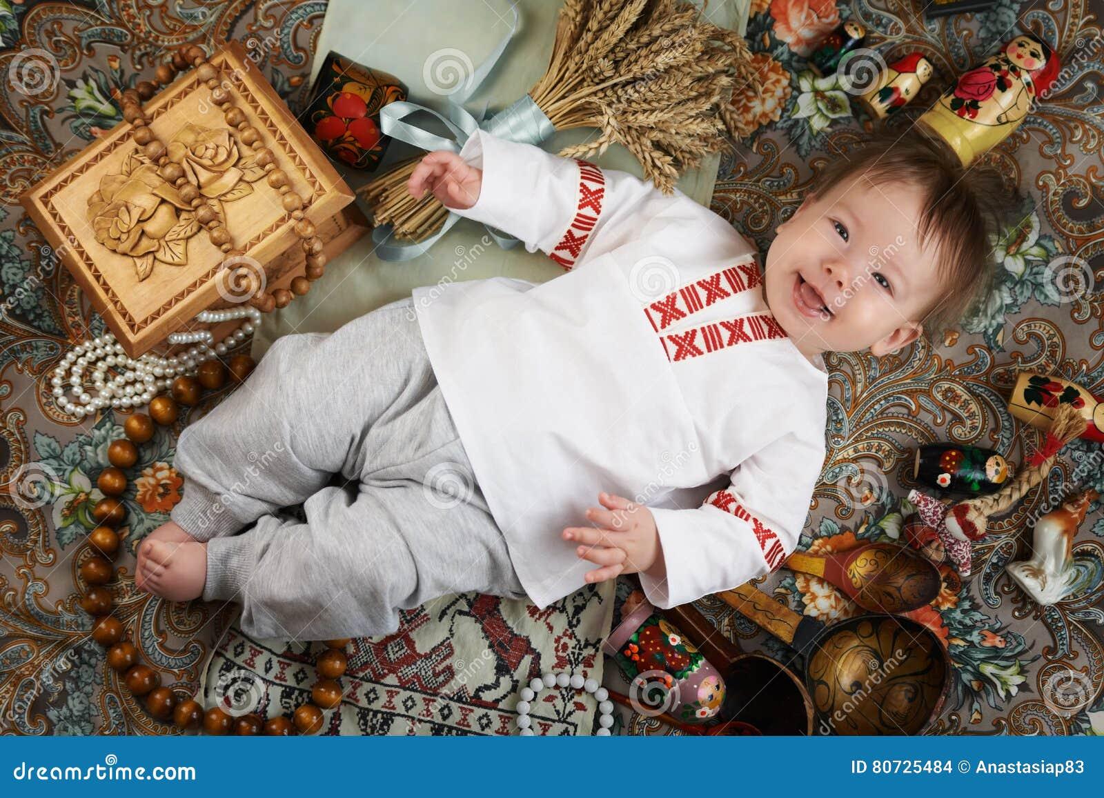 Мальчик в традиционной русской рубашке окруженной русскими антиквариатами