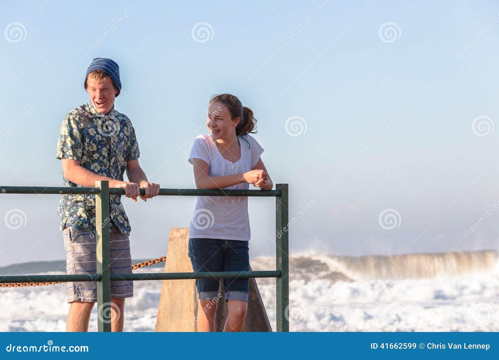 Мальчик девушки подростков говоря приливные океанские волны бассейна