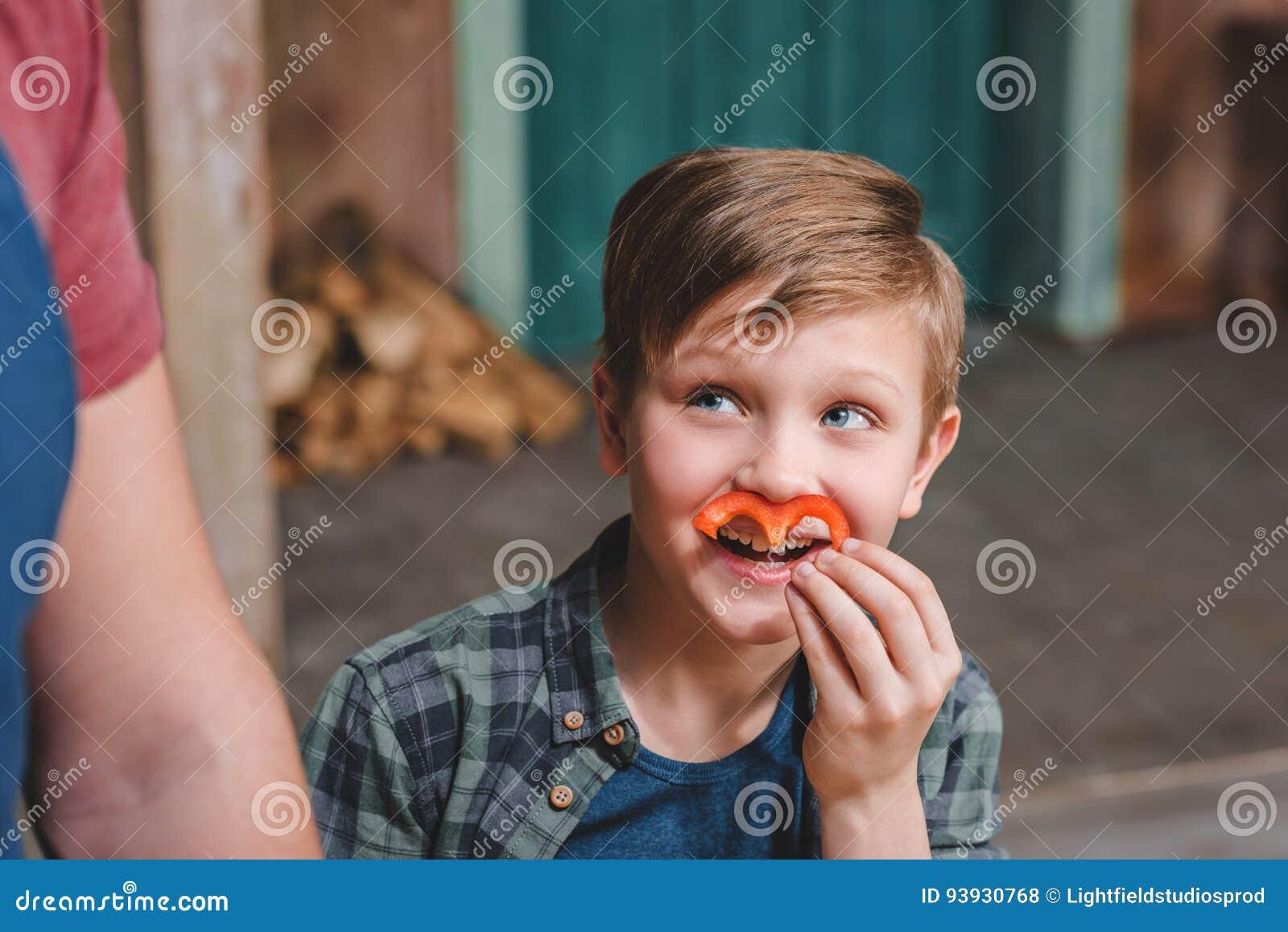 Мальчик держа кусок перца как усик и смотря прочь