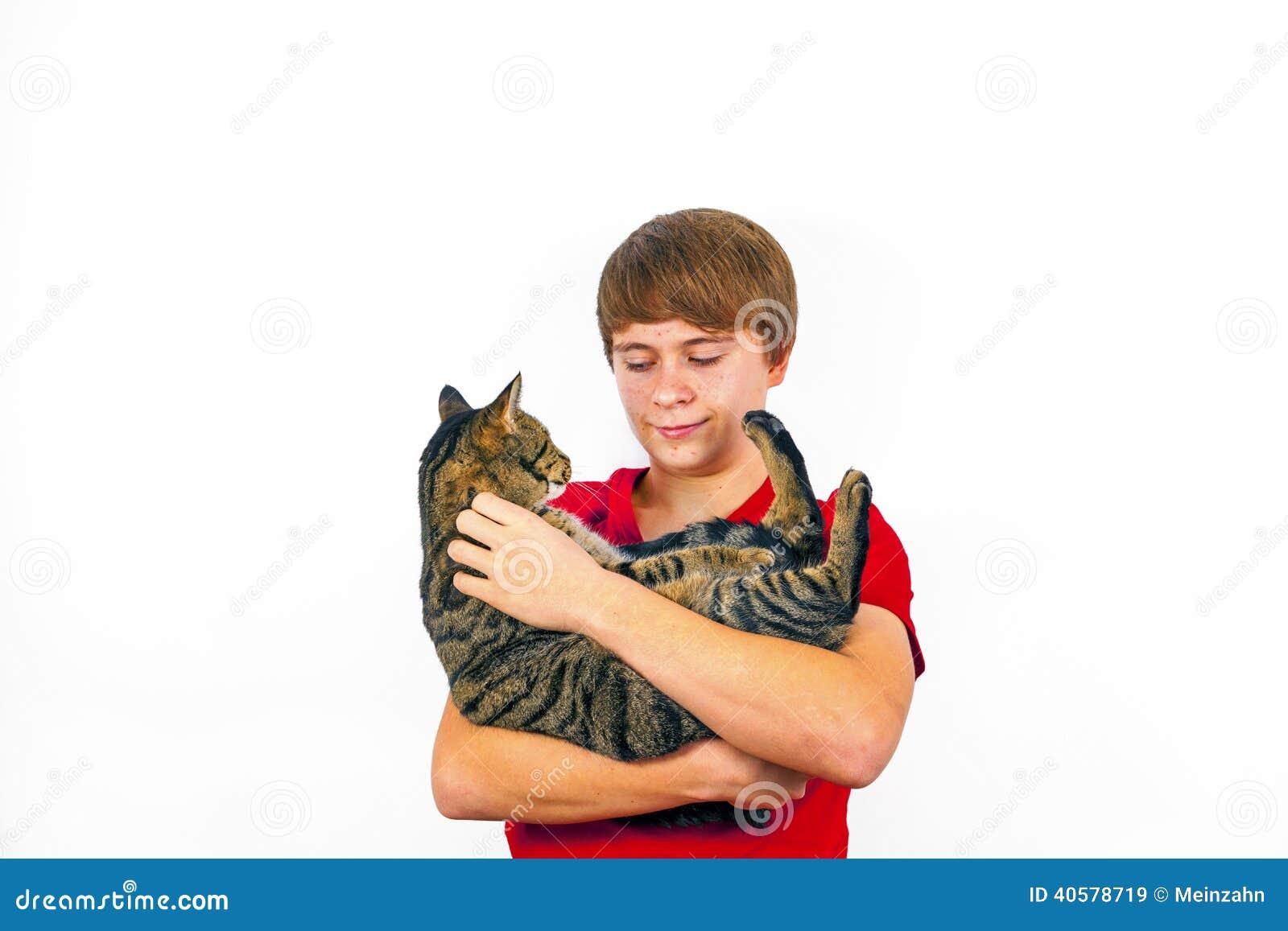 Мальчик держит его кота tabby в его оружиях