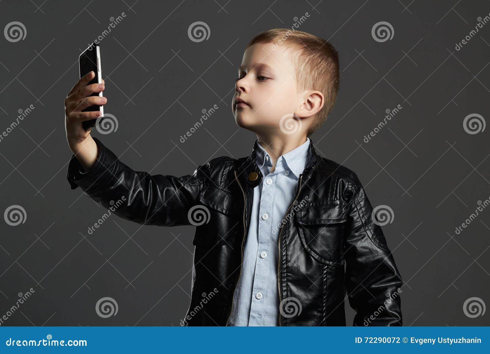 Мальчик делая selfie стильный ребенок в кожаных пальто и шляпе Ягнит эмоция