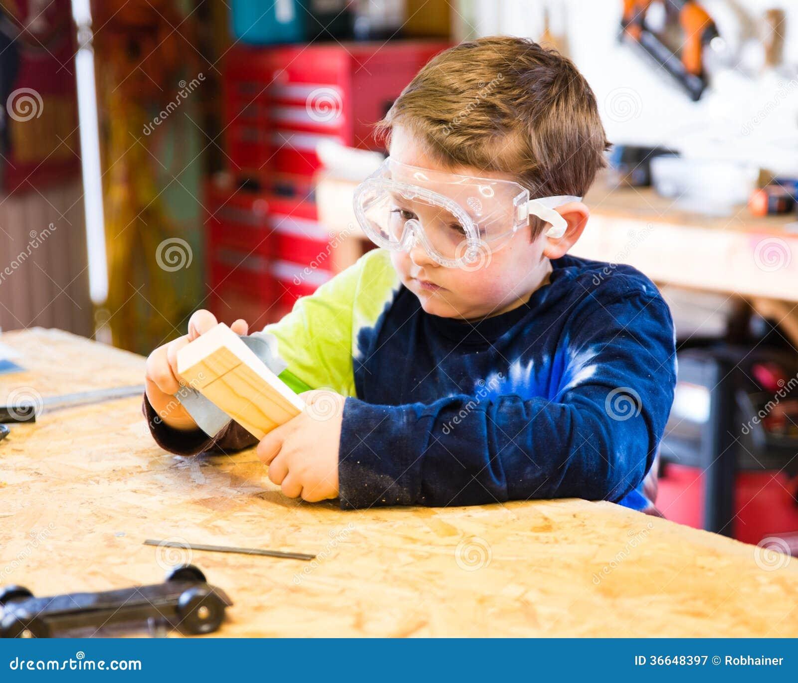 Мальчик зашкурить деревянный блок в мастерской