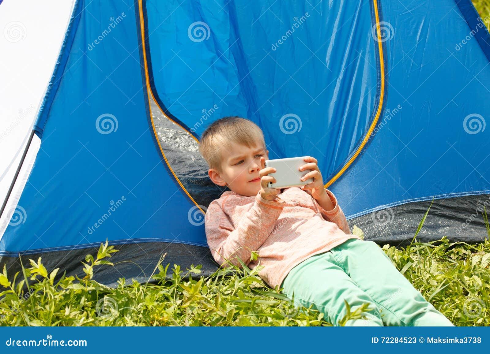 Download Мальчик играет мобильный телефон в парке лета Стоковое Изображение - изображение насчитывающей outdoors, удерживание: 72284523