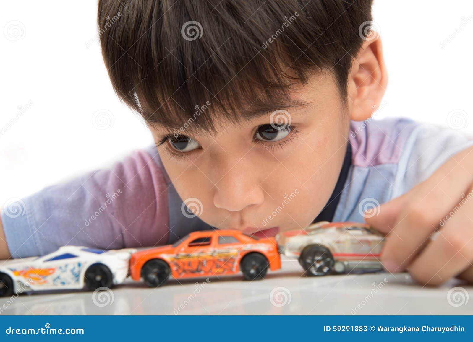 Мальчик играя с игрушкой автомобиля на таблице самостоятельно
