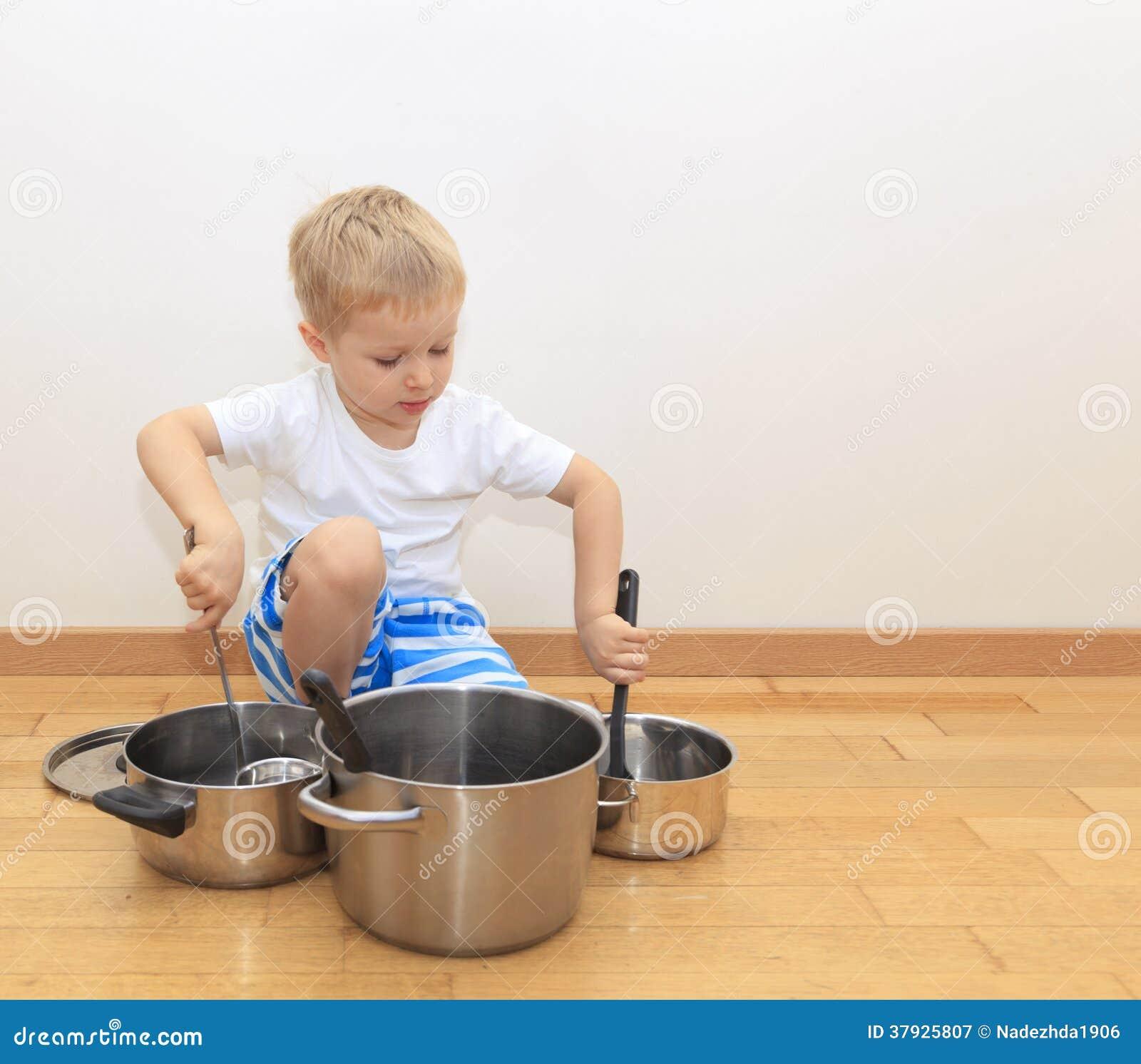 Мальчик играя с утварями кухни