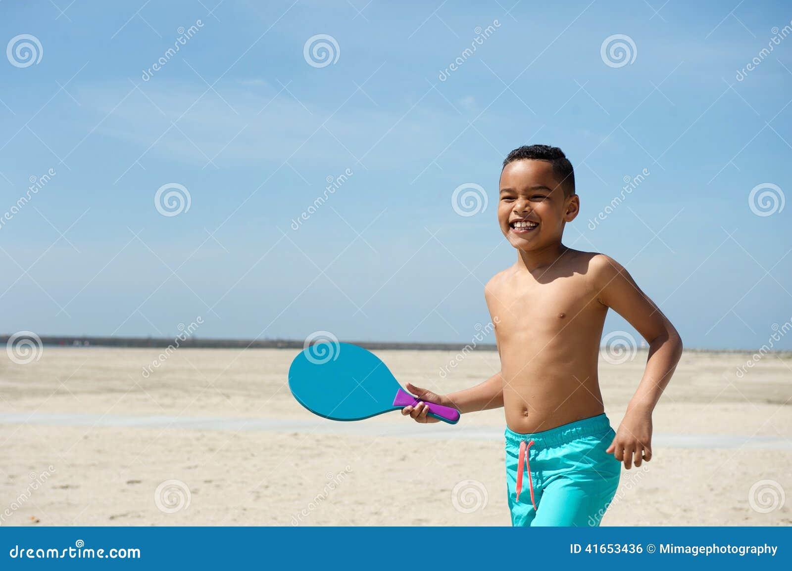 Мальчик играя шарик затвора на пляже