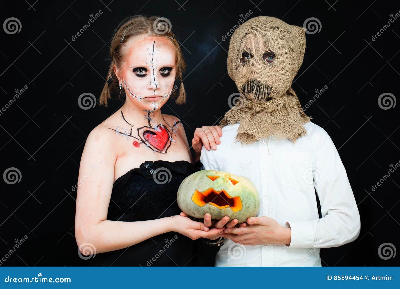 Мальчик и девушка при состав хеллоуина держа тыкву