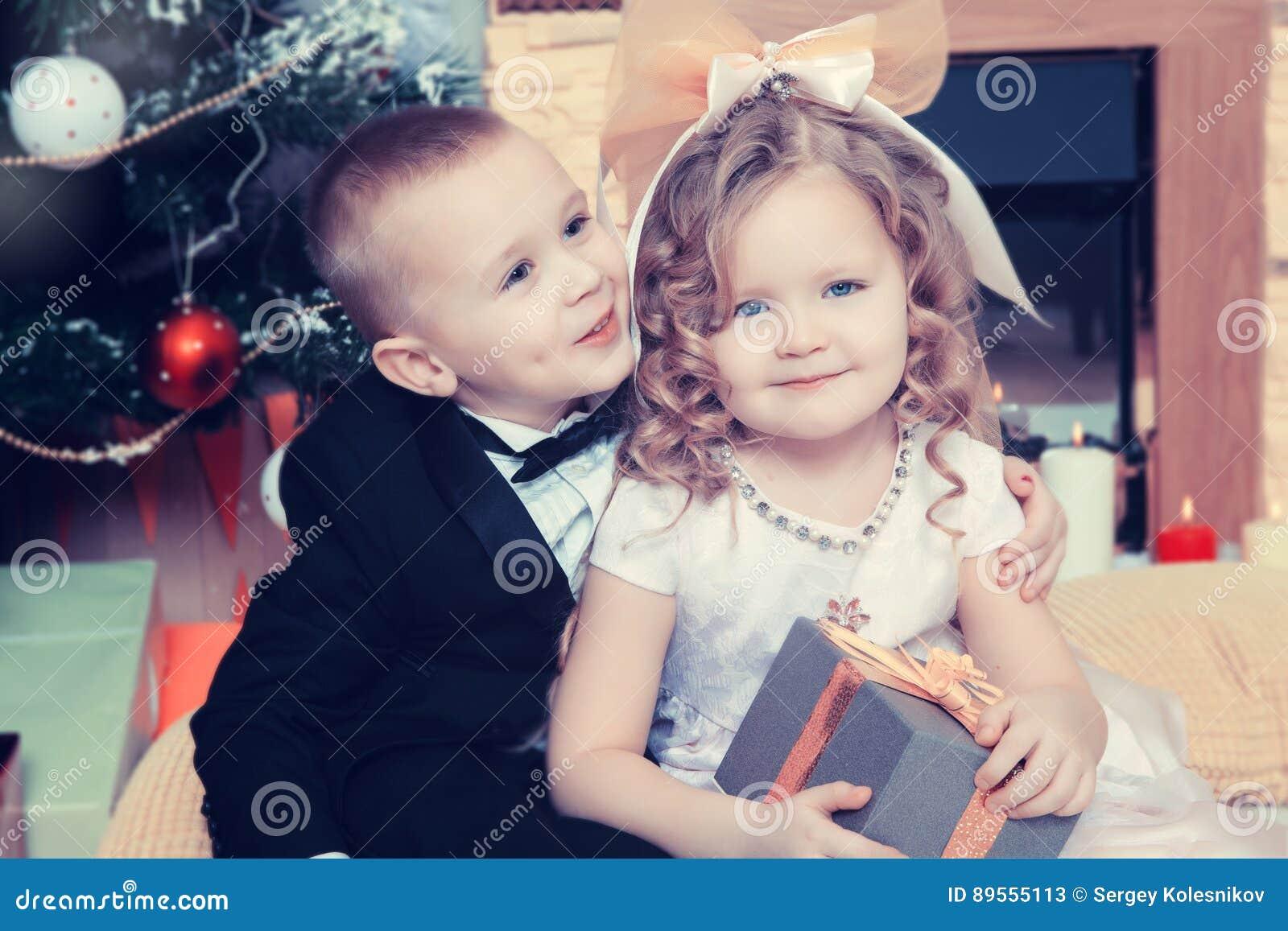 Мальчик и девушка с подарками около рождественской елки