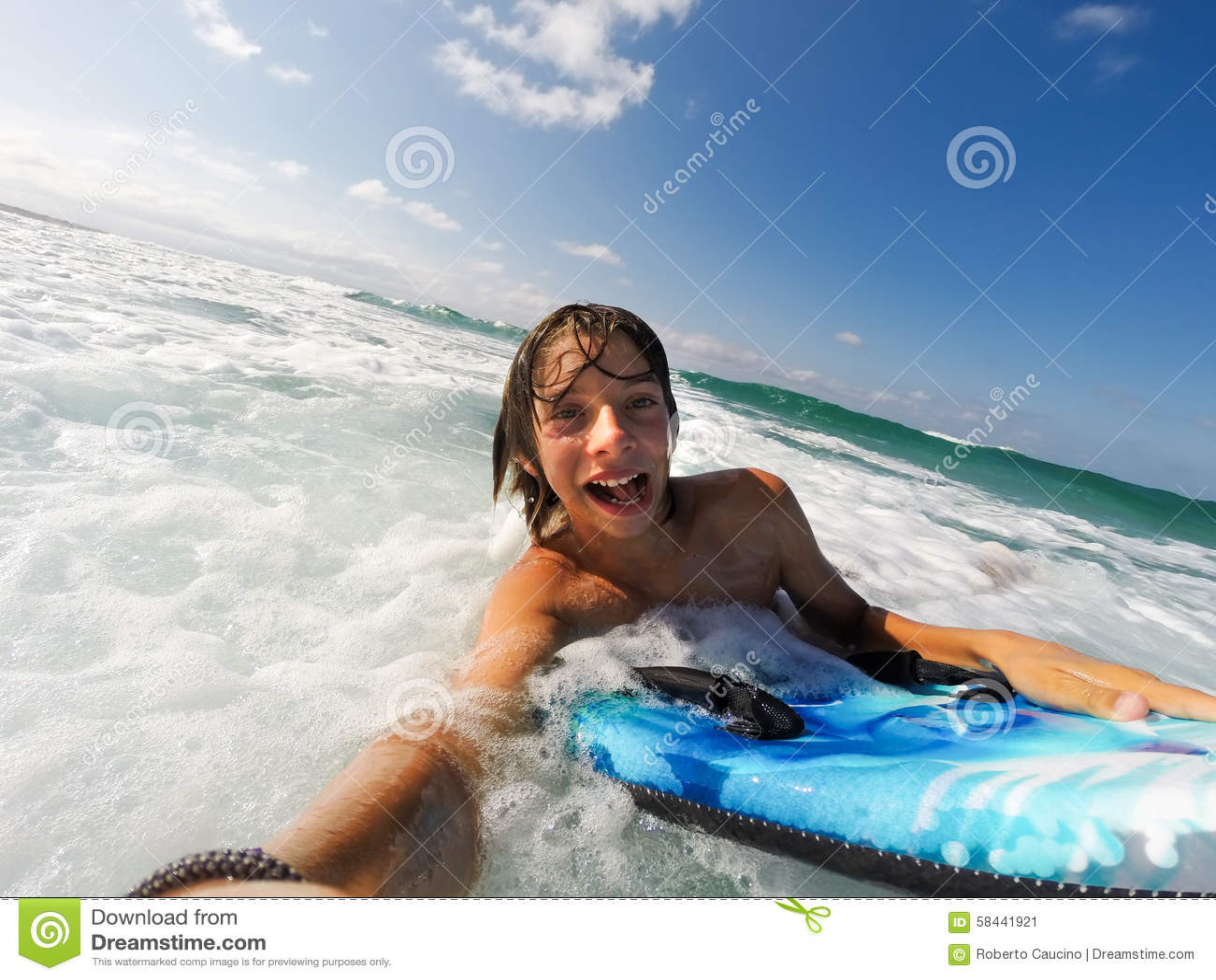Мальчик наслаждается ехать волны с surfboard